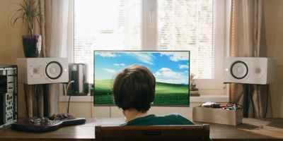 boy in red shirt sitting on chair in front of black flat screen tv