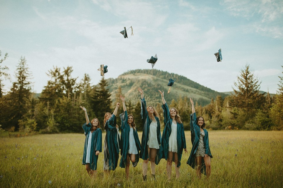 graduates standing in a field throwing caps