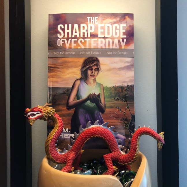 A small red dragon guarding a paperback copy of The Sharp Edge of Yesterday in a wooden yarn dish filled with glass beads.