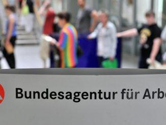 Besucher der Agentur für Arbeit warten an einem Schalter. Foto: Hendrik Schmidt/Archiv