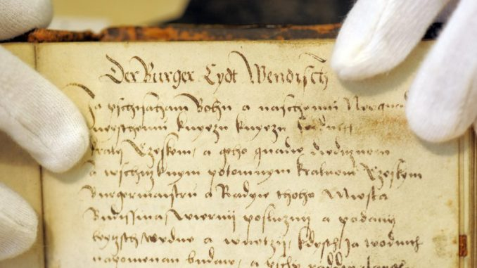 Die Stadtarchivarin präsentiert den Wendischen Bürgereid von 1531. Foto: Matthias Hiekel/Archiv