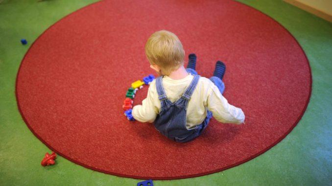 Ein Kind spielt in einer Kinderkrippe auf dem Boden. Foto: Julian Stratenschulte/Archiv