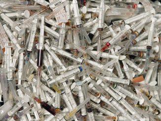 Gebrauchte Spritzen liegen in einem Sammelcontainer. Foto: Boris Roessler/Archiv
