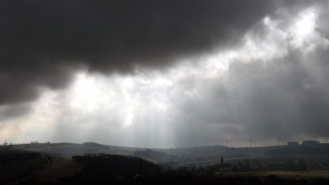 Dunkle Wolken ziehen über die hügelige Landschaft. Foto: Hendrik Schmidt/Archiv