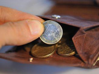 Eine Hand nimmt eine Euro-Münze aus einem Geldbeutel. Foto: Andreas Gebert/Archiv
