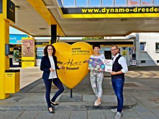 Antje Herrmann von Sonnenstrahl e.V. und Simone Saloßnick, Inhaberin der Dynamo Fan Tankstelle, nehmen die Sonderbriefmarke von Alexander Hesse, Marketingleiter bei PostModern, entgegen (v.l.n.r.). (Foto: ©PostModern)