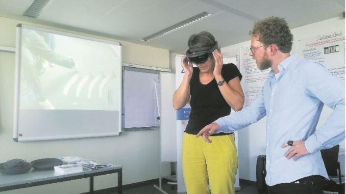 TÜV Rheinland Mitarbeiter Nils Brüggesch zeigt einer Berufskundeschulungsteilnehmerin die Funktion der Hololens. Fotos: PR