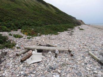 En optimistjolle er totalt smadret, og der ligger stolper fra kommunens trappe længere henne ad stranden