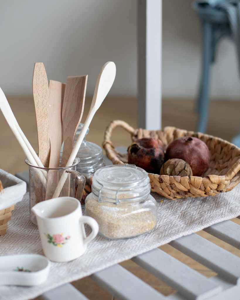 white ceramic mug beside clear glass jar on brown wooden table