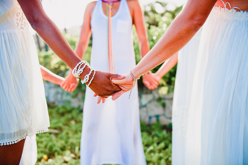women joined together and united in community, holding hands