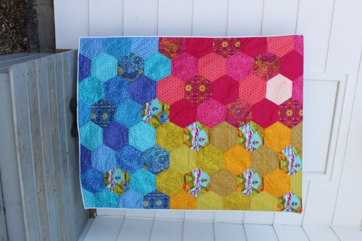 A hexagon quilt with eight inch hexagons grouped in blocks of color of pink, yellow and blue.