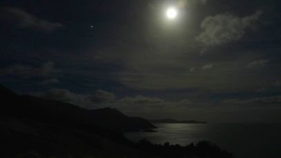 The moon shines brightly on a calm ocean