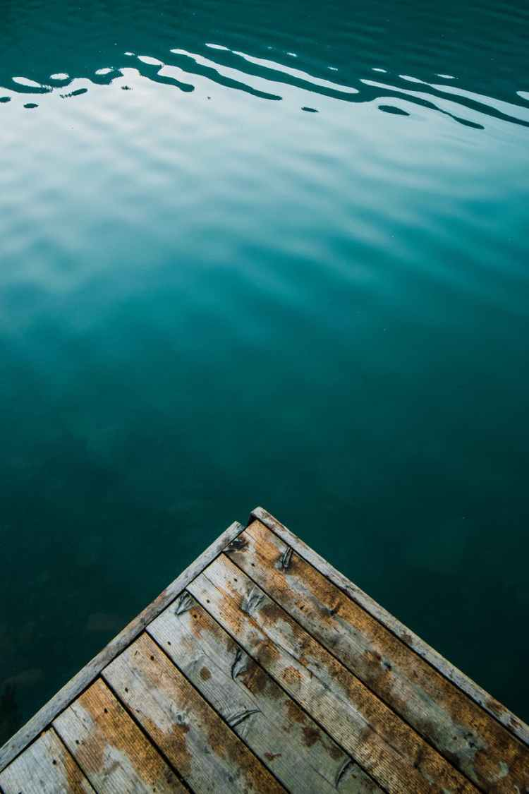wooden pier corner above calm rippling lake
