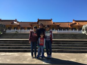 mother and three boys in front of a large temple