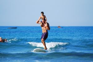 father and son on a surfboard