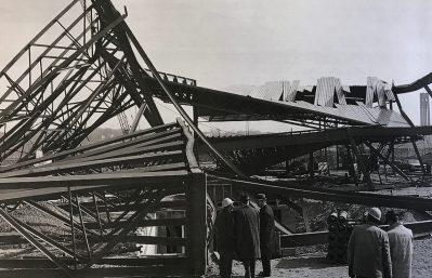 Picture shows men looking at a portion of the wreckage of the arena under construction