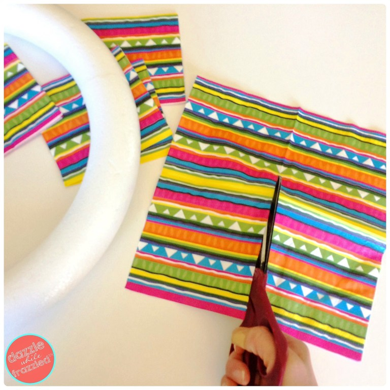 Cut fiesta themed cocktail napkins in half to wrap around a DIY Cinco de Mayo Margarita Day wreath