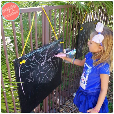 Use plywood scraps and chalkboard paint for DIY outdoors chalkboard on fence for kids.