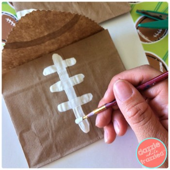 Use white paint and brown paper bags to make DIY football snack bags for DIY football party | DazzleWhileFrazzled.com