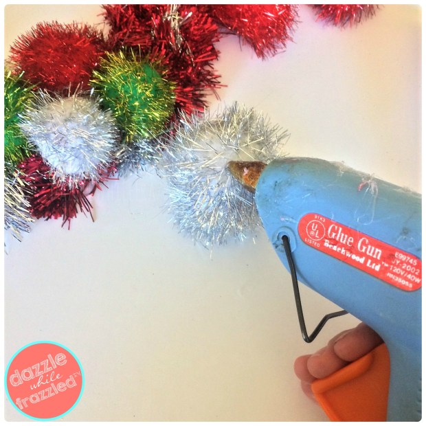 Hot glue gun jumbo sparkly pom poms onto a retro DIY tinsel garland Christmas wreath