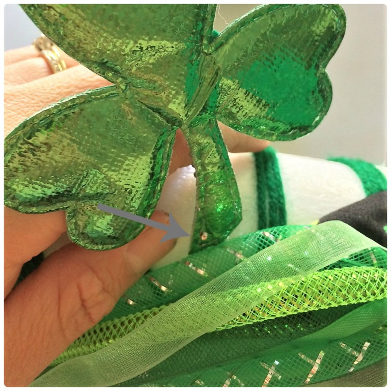 Dollar store shamrocks pinned to top of foam wreath for St. Patrick's Day decor