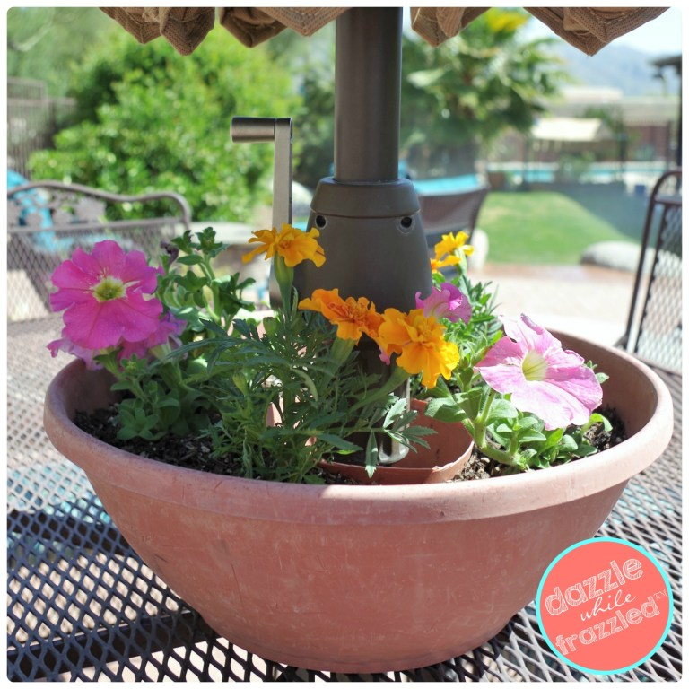 Decorate your outdoor patio with a DIY flower pot around a patio table umbrella.