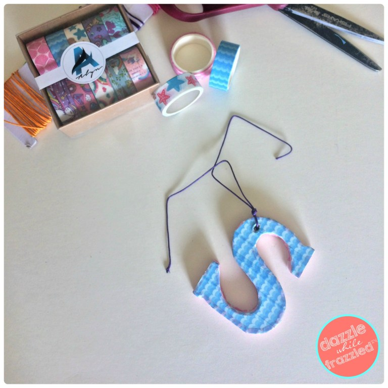 Insert braiding cord into wooden letter covered with washi tapes to hang onto a purse or kids school bag.