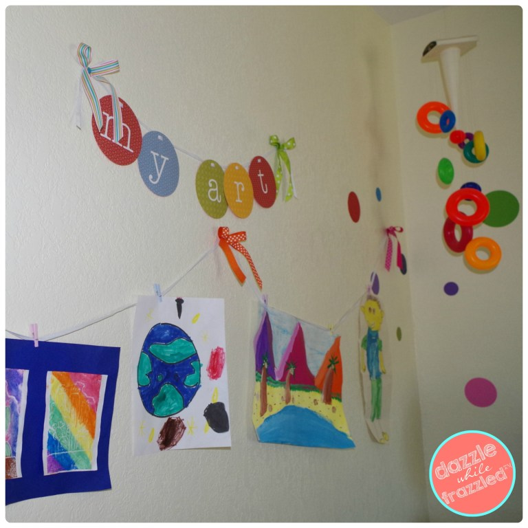 Create easy kids rotating art gallery with ribbon and small clips on the wall of a DIY kids toy room.