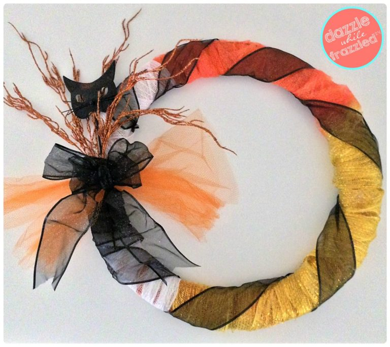 Use orange, yellow, white mesh tulle and black ribbon to make a candy corn Halloween front door wreath.