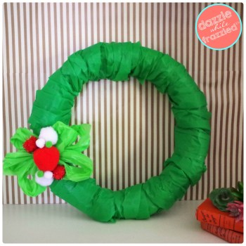 Affordable Christmas wreath decoration using dollar store plastic tablecloth and pom poms.