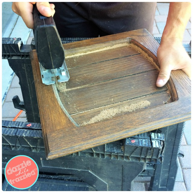Use jigsaw to remove inlays within old kitchen cabinet for DIY Little Free Library.