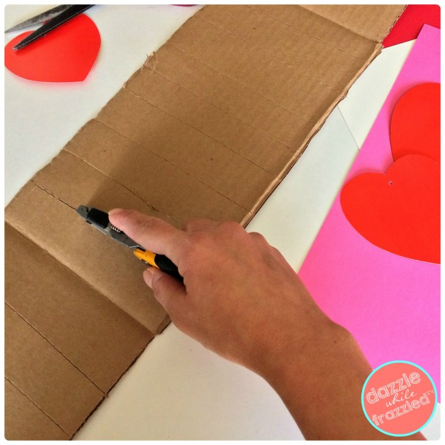 Score strip of cardboard to make round shape for DIY kids Valentine's Day wedding cake card holder.