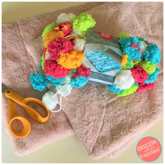 Use blanket throw and pom pom doodle yarn to make DIY blanket with pom pom accessories for kids and home decor.