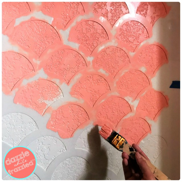 Use small paint brush to stencil fish scale pattern by Stencil Revolution onto wall for DIY kids closet reading nook.