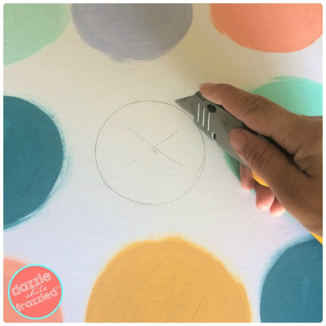 Use an Exacto knife to cut circle shape out of white art board where Nest thermostat will be placed within DIY wall art to hide ugly wall thermostats.
