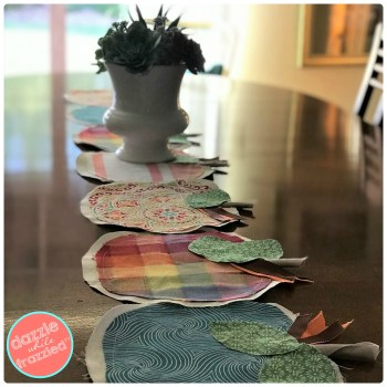 Get a colorful farmhouse Thanksgiving table with DIY fabric scraps pumpkin-shaped table runner.
