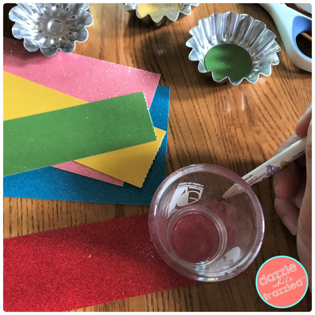 Cut out cardstock paper circles to glue onto bottom of tart tins for DIY colorful Christmas tree ornaments.