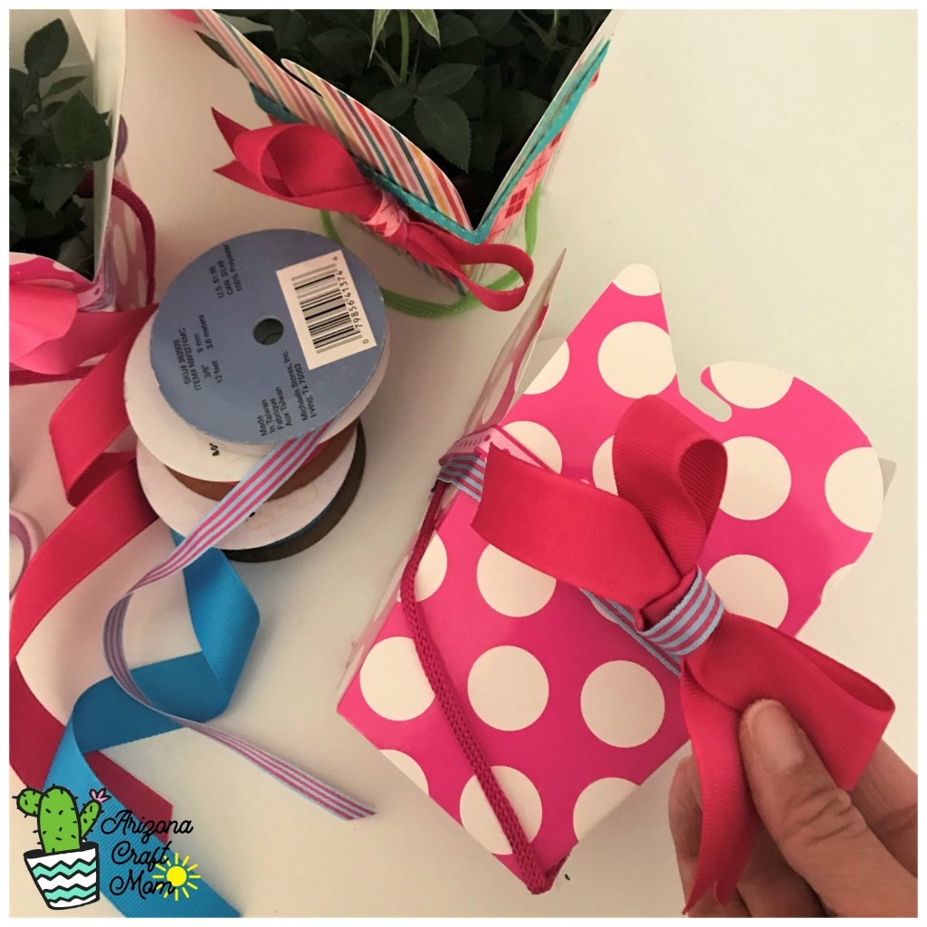 Decorate paper party favor boxes with grosgrain ribbon for DIY potted plant gifts for teachers, coaches and friends.