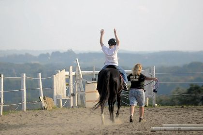 Joe Gallucci, 10, stretches his arms above his head as he works on balance during a horse-riding therapy session at Horse 'N Soul in Washington County.