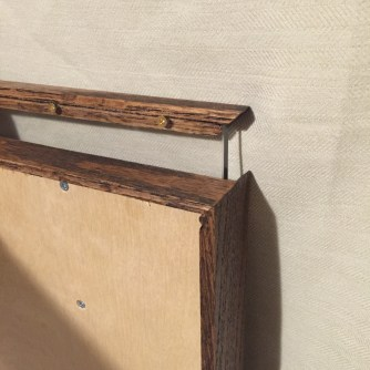 Detail of back showing the handle attached to the glass from the back with brass screws.