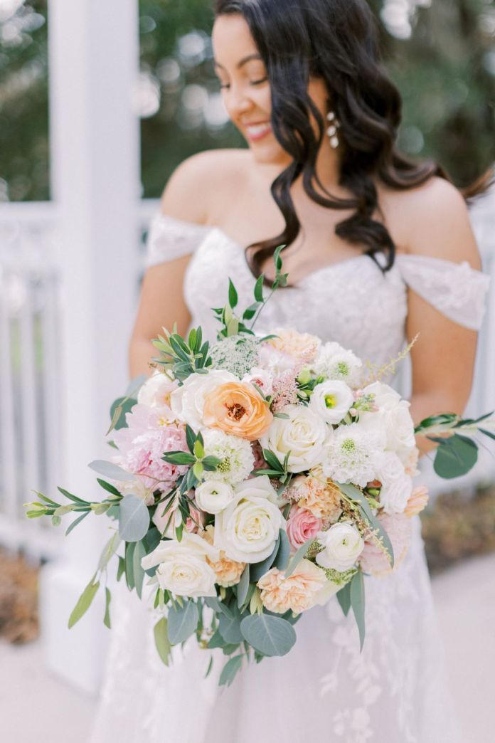 Bride holds beautiful bouquet of blushing colored flowers