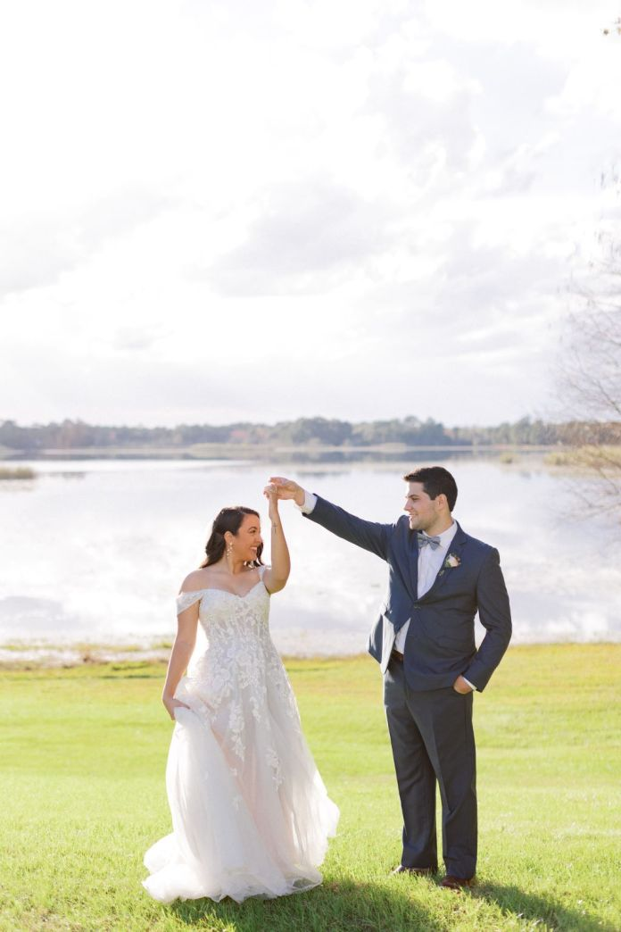 Groom whirling bride in front of the water