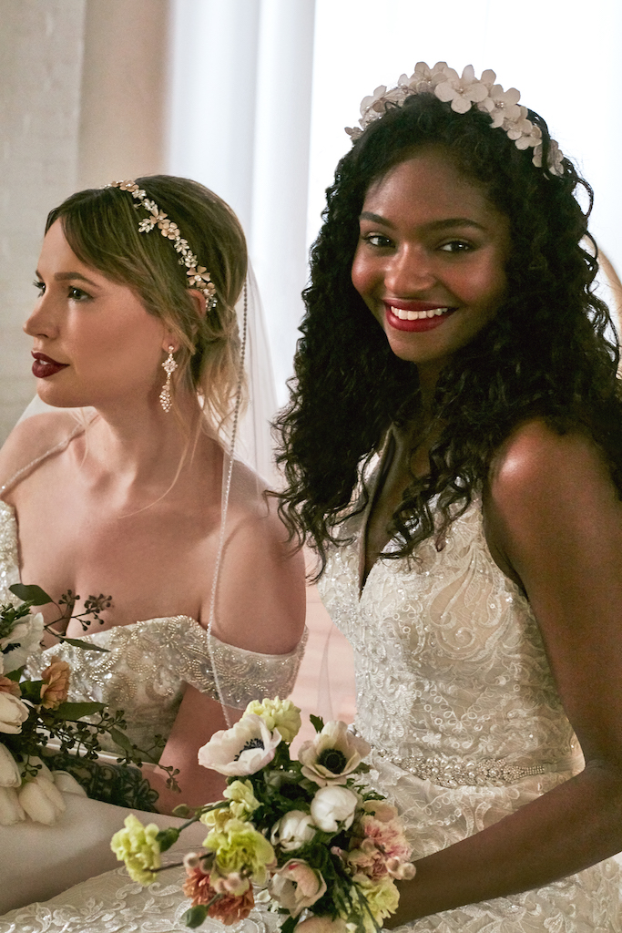 two brides in wedding dresses with pearl and flower accessories