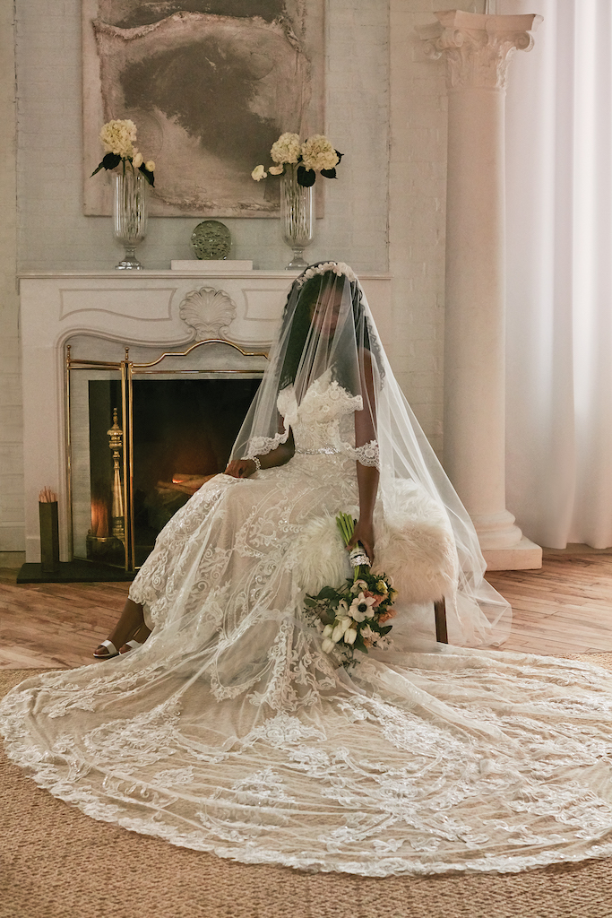 Bride wears an ornate wedding dress with a cathedral-length train