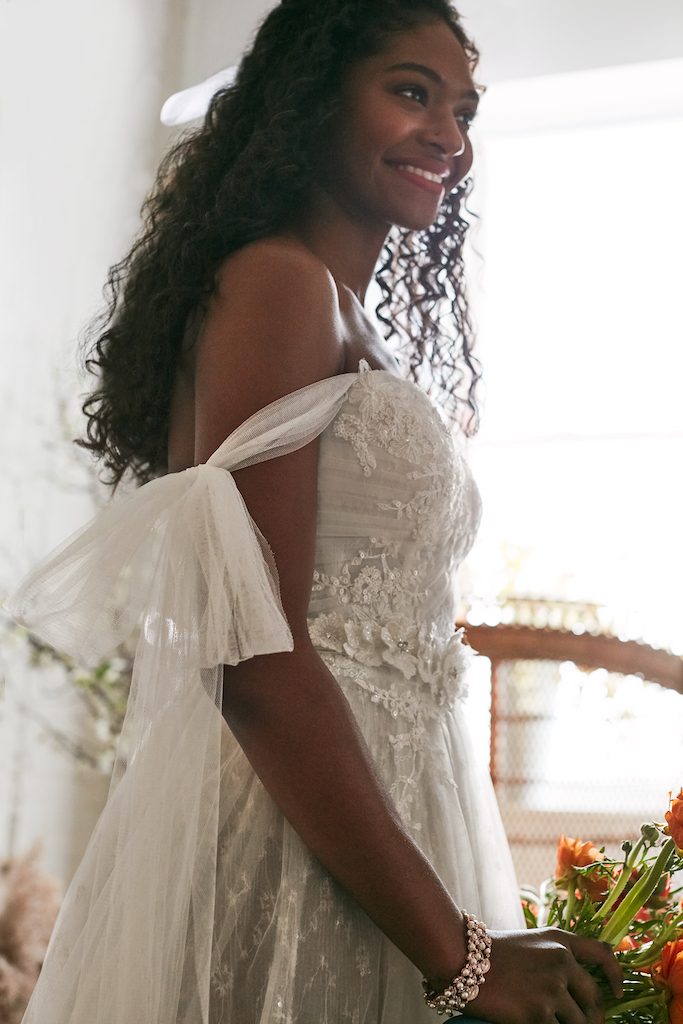 Bride in a wedding dress made of tulle, decorated with pearls, sequins and crystals