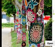 line of tress that have been yarn bombed with wool patterns around the trunks