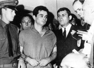 A Black & White Picture of a Man in handcuffs, surrounded by police and politicians of the Greek Junta
