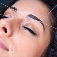attractive woman in beauty salon on facial hair removal eyebrow threading procedure