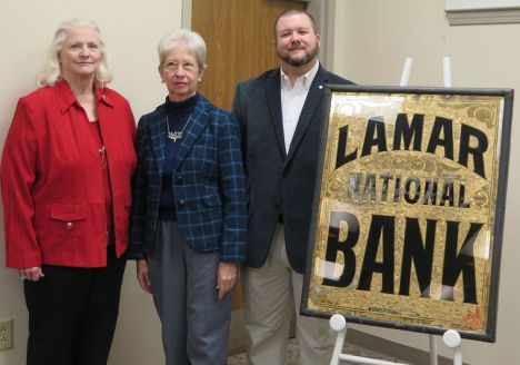 Loris Flowers and Jane DuBose, members of the Darlington County Historical Commission Board, stand with Brian Gandy, Director/Historian, after the unveiling of the restored sign that hung over the Lamar National Bank, which was chartered in 1912. THe refurbished sign will now hang outside the conservation romm at the Historical Commission on Hewitt Street, Darlington.