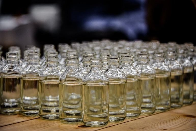 A batch of glass vials filled with hand sanitizer ready to be capped